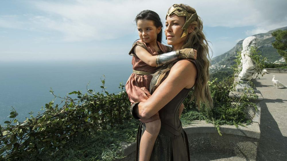A rainha amazona Hipólita (Connie Nielsen) segura a sua pequena Diana (Lilly Aspell) | Crédito: Divulgação